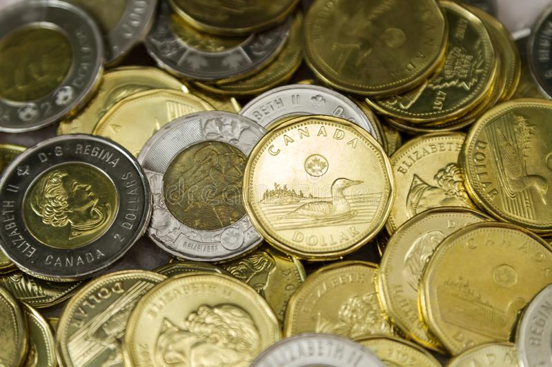 Canadian $1 dollar coins or loonie and $2 dollar coins or toonie. Canadian $1 and $2 dollar coins. The Canadian one dollar coin, commonly called the loonie. It stock photos