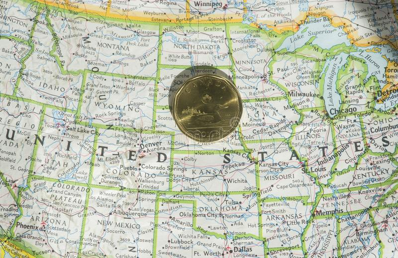 Canadian dollar. A Canadian one dollar coin is shown on a map of the United States stock photo