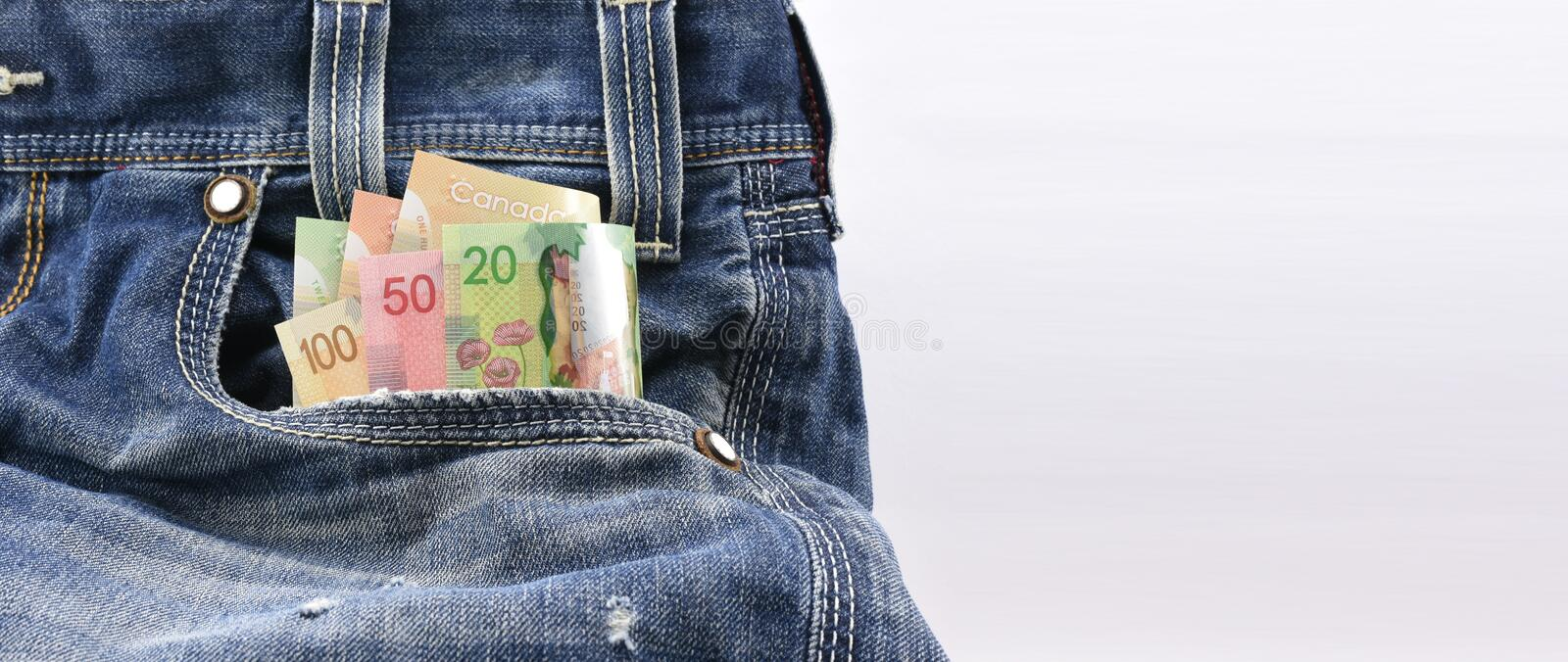Canadian dollars of value 20, 50 and 100 in Blue Denim Jeans Pocket, Concept on earning money, saving money. Sales with ample empty space for text message on royalty free stock photos