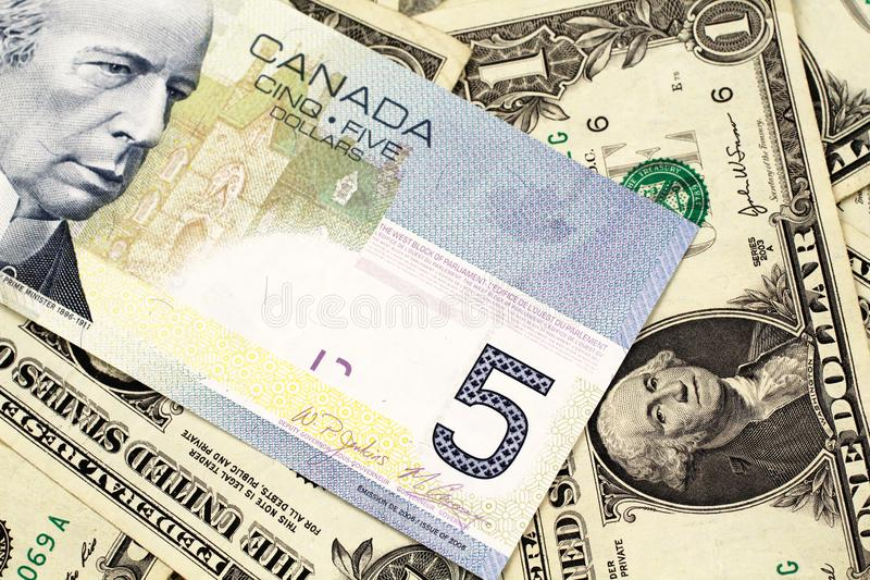 A Canadian five dollar bill on a background of dollar bills. A macro image of a blue Canadian five dollar bill on a background of American one dollar bills close stock photo