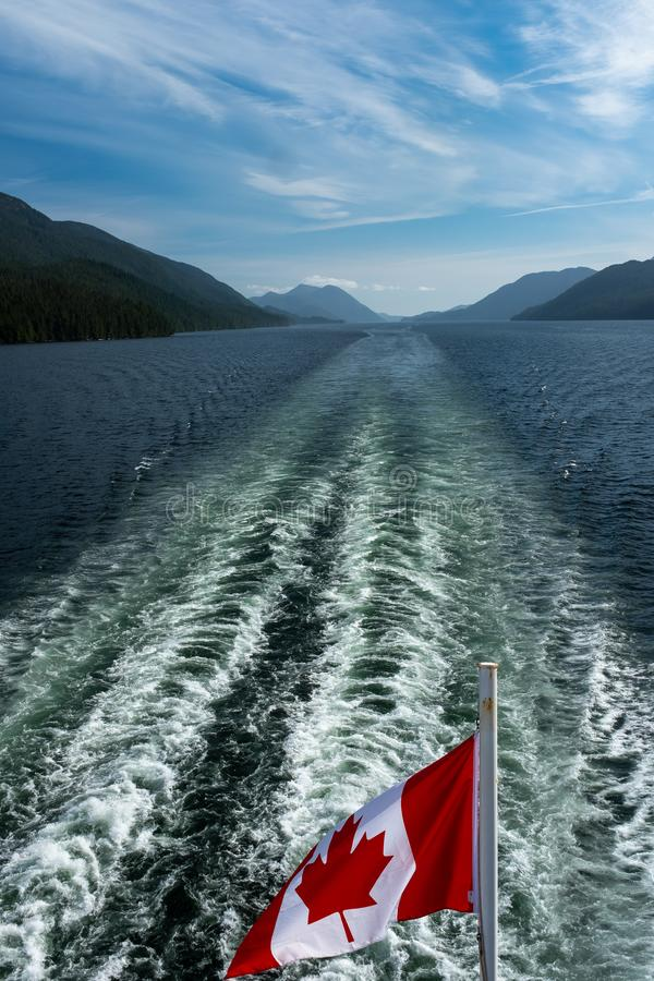 The Canadian flag flying in the wind at the back of ferry as the boat makes it way through the Inside Passage. With the wake, portrait aspect stock image