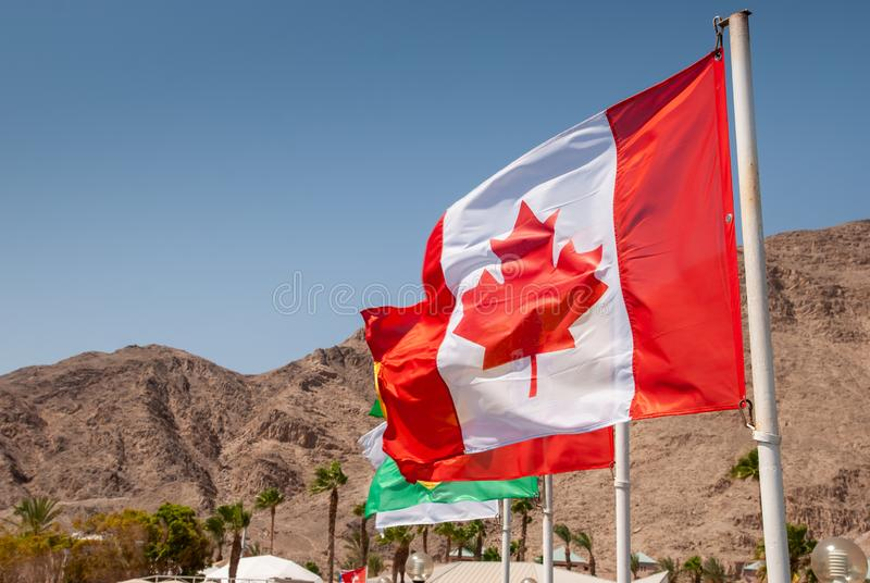 Canadian flag waving on mountains and blue sky background. Canadian flag waving on Eilat mountains and blue sky background stock photos