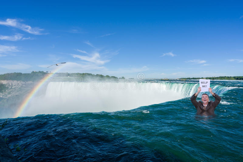 Canadian Horseshoe Falls at Niagara. Man holding help me sign in the air while standing in the water at the top of Horseshoe waterfall from Canadian side of royalty free stock photography