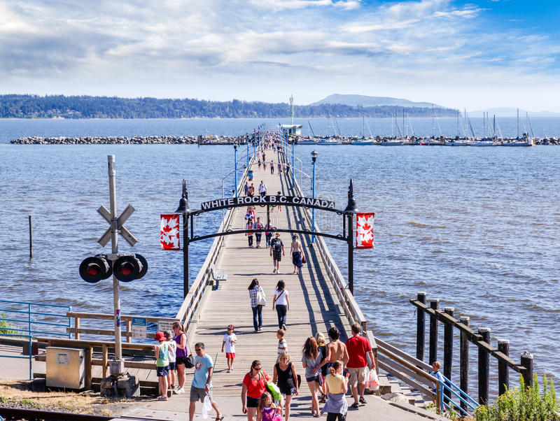 Canadian Landmark: White Rock, British Columbia. Locals and tourists stroll along the famous 1,500 ft. long pier in White Rock near Vancouver, British Columbia stock photography