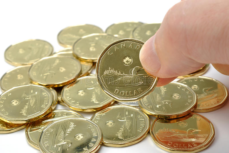 Canadian One Dollar Coin. Man picking a one dollar coin stock photography