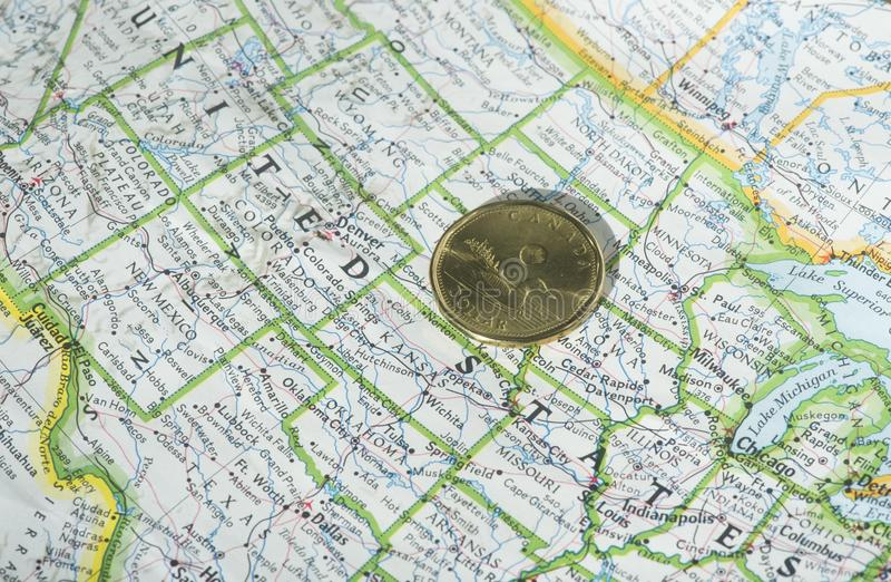 Canadian dollar. A Canadian one dollar coin is shown on a map of the United States royalty free stock photography