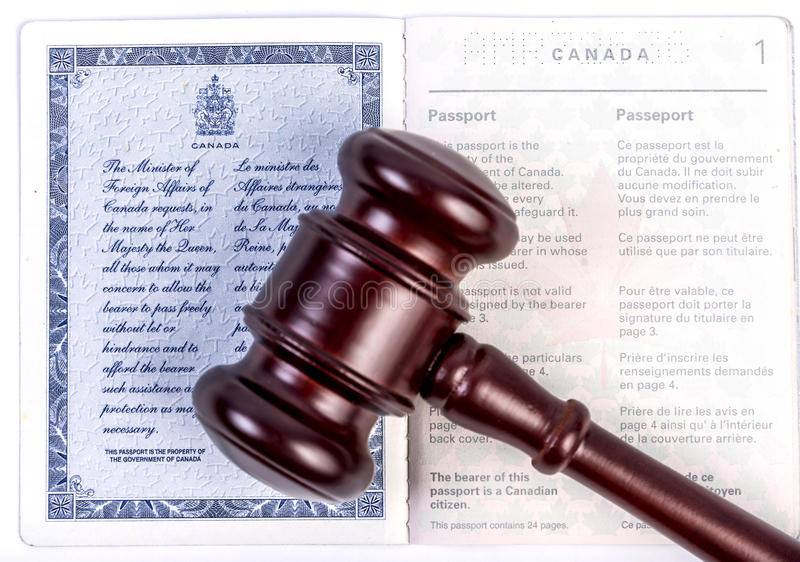 Canadian passport with gavel. Open canadian passport withgavel on white background royalty free stock photography