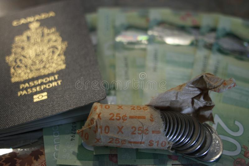 Canadian passport on twenty dollar bills and next to canadian coins. Theme of travel or immigration royalty free stock photo
