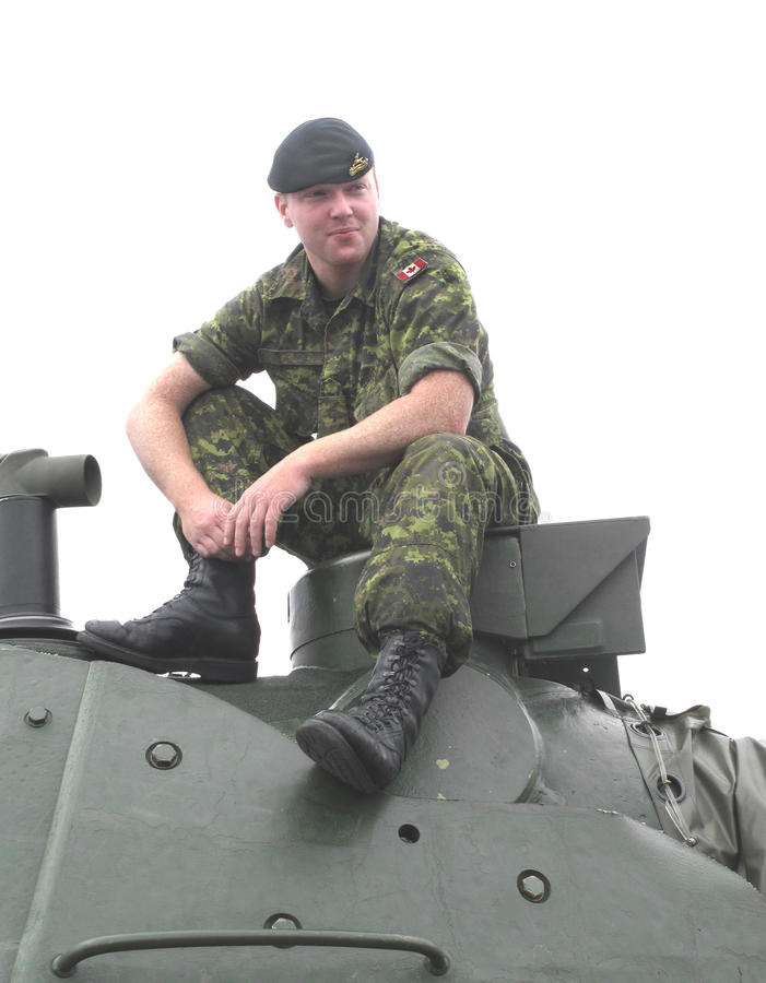 Canadian Soldier. Canadian male soldier, wearing camouflaged fatigues and a beret, resting on the turret of a tank. Isolated on white stock photography