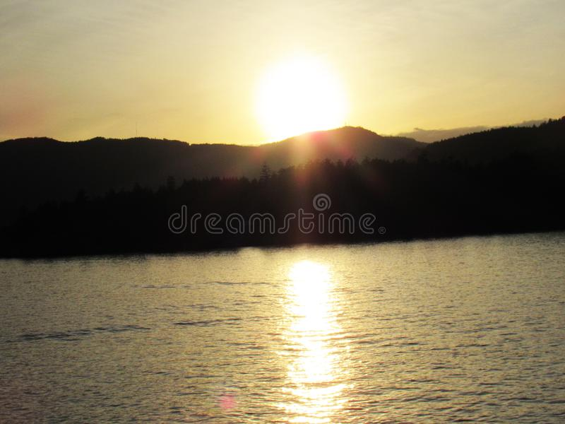 Canadian Sunset Behind Mountains Glistening on Ocean. Sunset Over Ocean in Victoria, British Columbia, Canada stock photography
