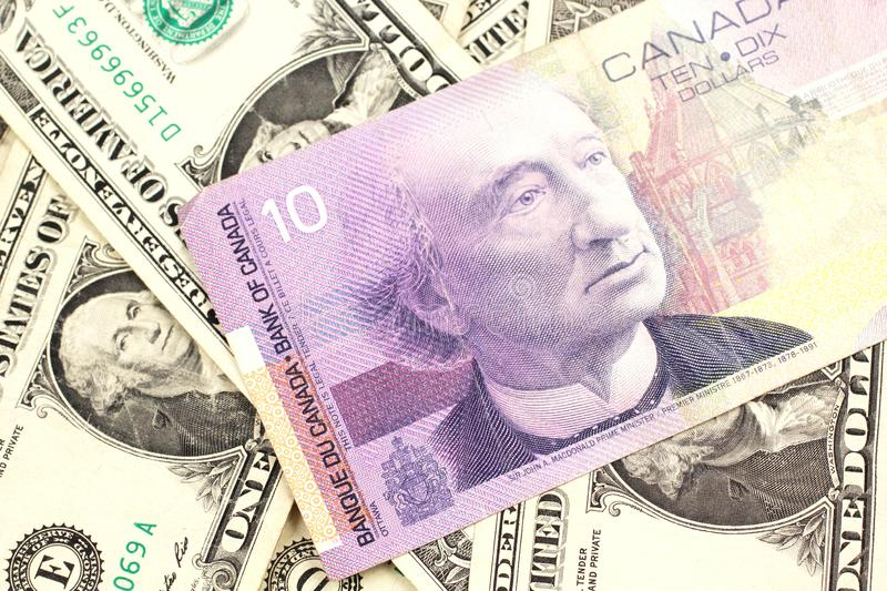 A Canadian ten dollar bill on a background of dollar bills. A macro image of a purple Canadian ten dollar bill on a background of American one dollar bills close stock image