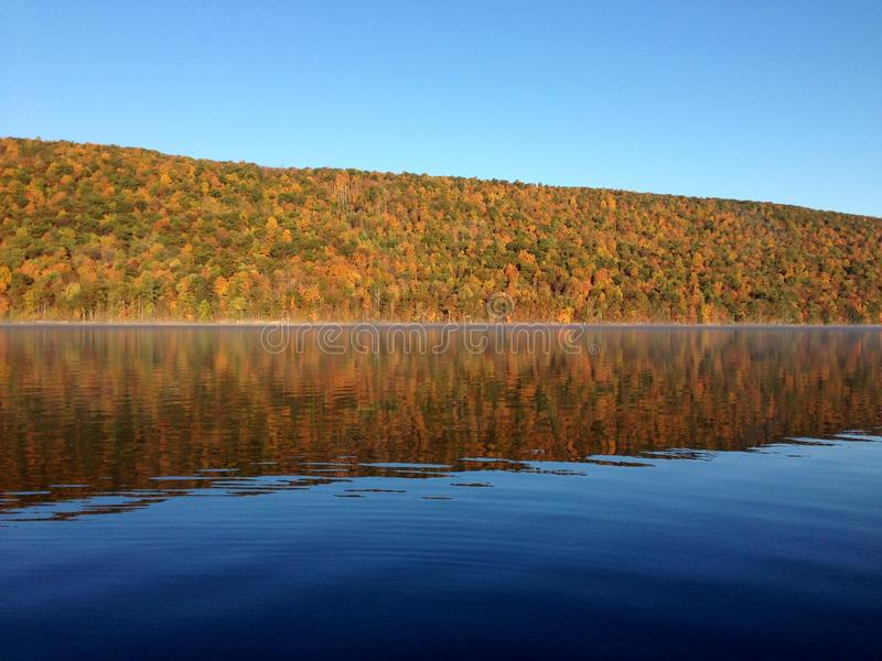 Canadice Lake, one of New York`s Finger Lakes. Bare trees on the shore of the clear, still water of Canadice Lake, one of Finger Lakes in New York, in horizontal stock photo