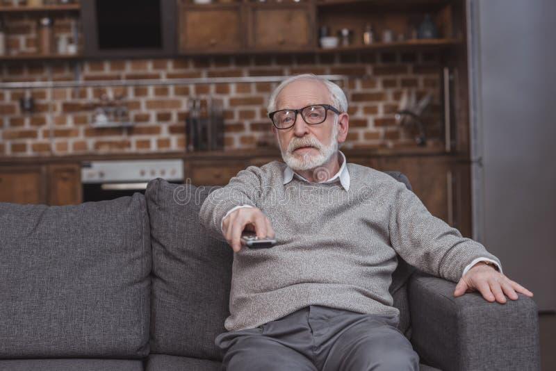 canais de televisão em mudança do homem cinzento considerável do cabelo com controlo a distância fotografia de stock