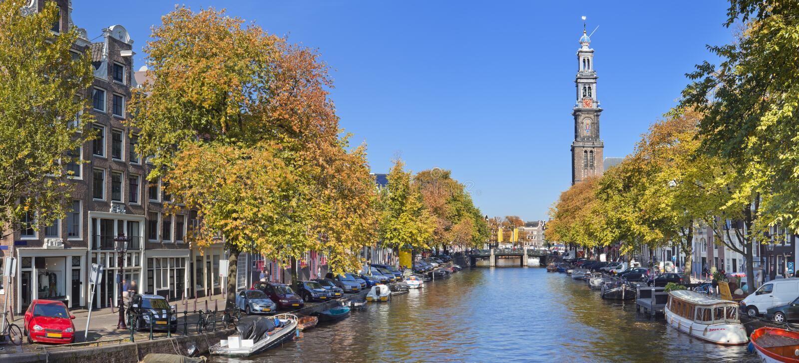 Canal in Amsterdam, The Netherlands in autumn. A canal with the Westerkerk tower in the city of Amsterdam, The Netherlands. Photographed on a beautiful day in royalty free stock photos