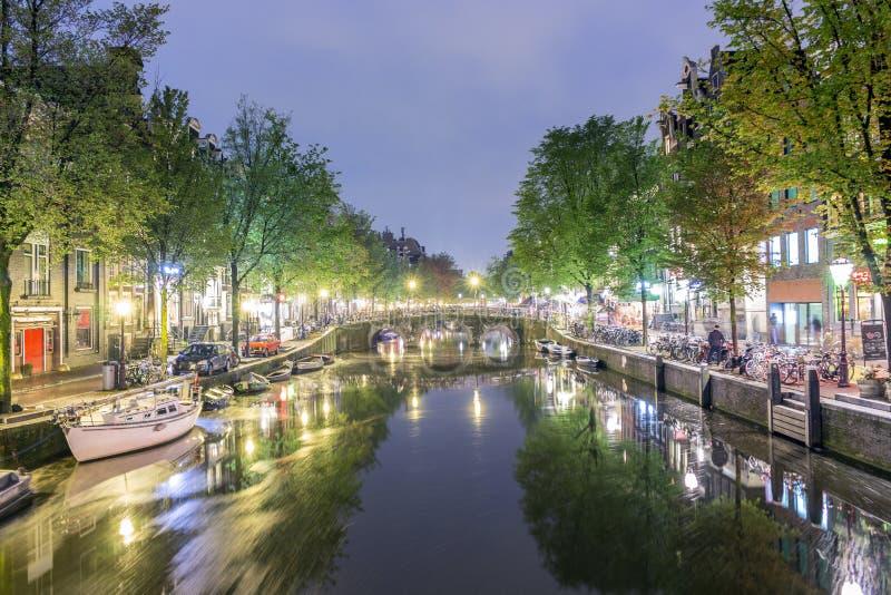 Canal avec des bateaux et des bicyclettes sur la rue la nuit à Amsterdam, Hollande photographie stock libre de droits