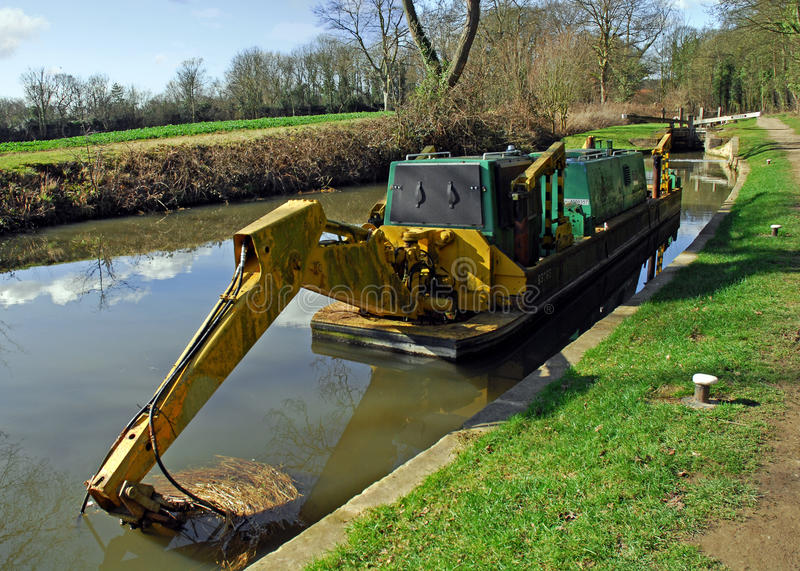 Canal Boat with Pneumatic Digging Arm. A canal boat with long pneumatic digging arm and bucket on a still sunny canal stock photography