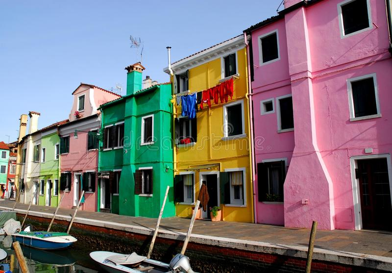 Canal with boats and colorful houses in Burano in Venice in Italy royalty free stock image