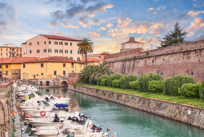 Canal with boats and walls of the old fortress in Livorno, Tuscany, Italy. View at dawn of the canal with boats and walls of the old fortress. Photo taken on stock photos