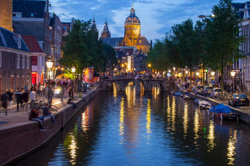 Canal with bridge, cathedral and boats in evening Amsterdam. Traditional dutch cityscape in twilight. stock photo