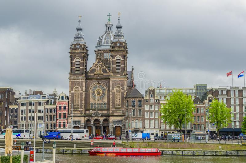 Canal and church of San Nicolas in front of the train station. Amsterdam netherlands holland royalty free stock photography