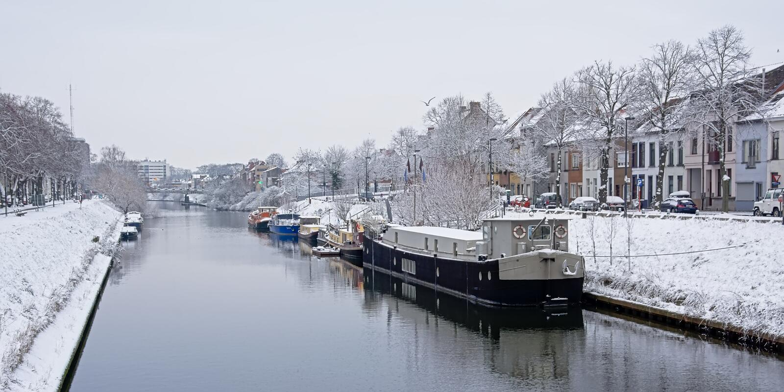 Canal in the city of Ghent with living boats on a winter day with snow stock image