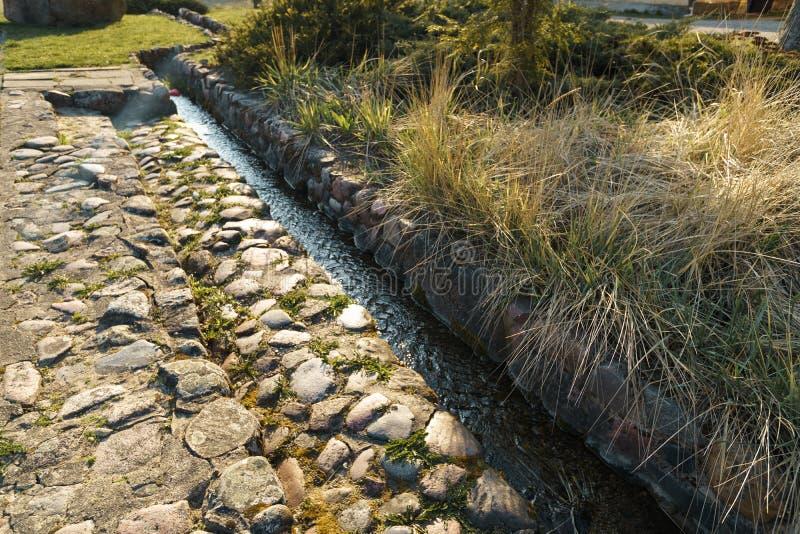Canal con el agua de manatial en la ciudad Sabile en Letonia imagen de archivo libre de regalías