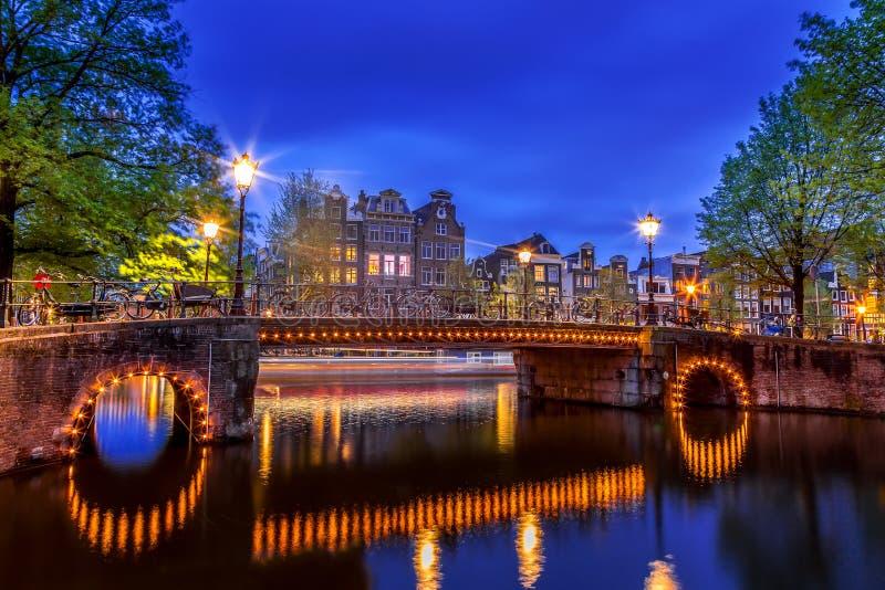 Canal de Amsterdam con las casas holandesas típicas y puente iluminado durante la hora azul crepuscular en Holanda, Países Bajos  fotografía de archivo