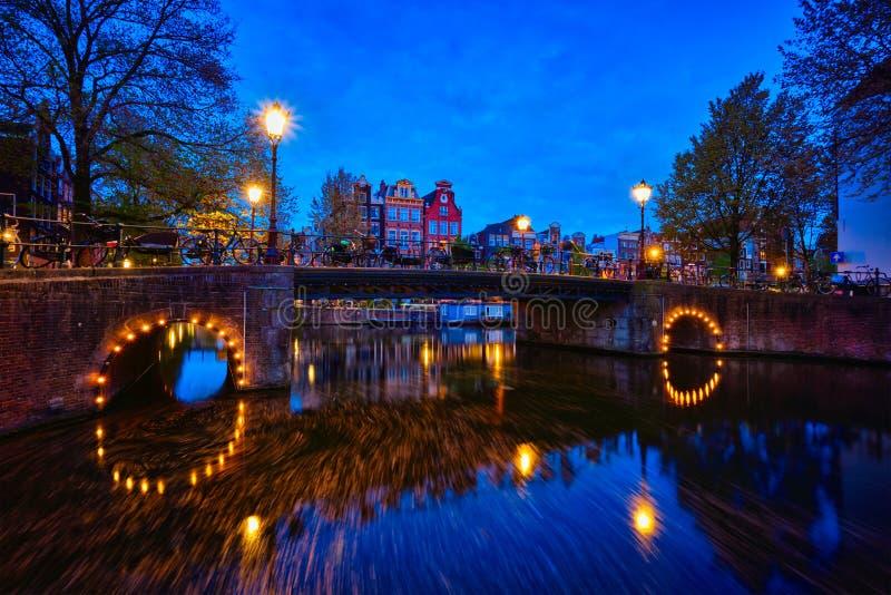 Canal de Amterdam, puente y casas medievales por la tarde fotos de archivo