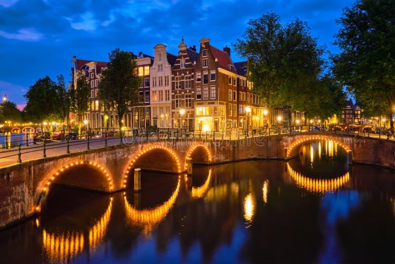 Canal de Amterdam, puente y casas medievales por la tarde foto de archivo libre de regalías