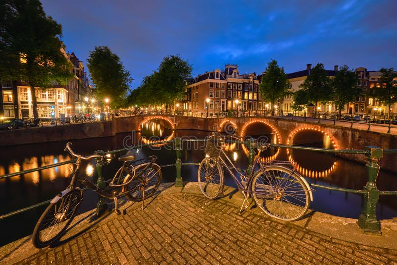 Canal de Amterdam, puente y casas medievales por la tarde fotos de archivo libres de regalías