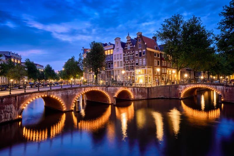 Canal de Amterdam, puente y casas medievales por la tarde foto de archivo