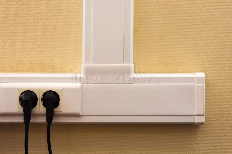 Canal de cable blanco con los mercados eléctricos en una pared amarilla, wh imagen de archivo