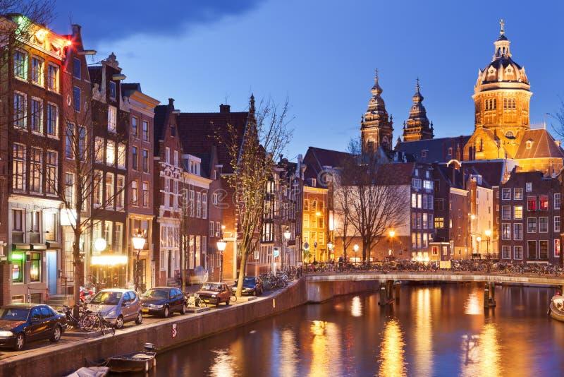 Canal en Amsterdam, los Países Bajos por noche foto de archivo