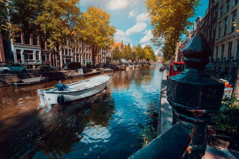 Canal en Amsterdam en luz del sol del otoño Barco que flota el canal arbolado, reflexiones vibrantes, nubes blancas en el cielo n foto de archivo libre de regalías