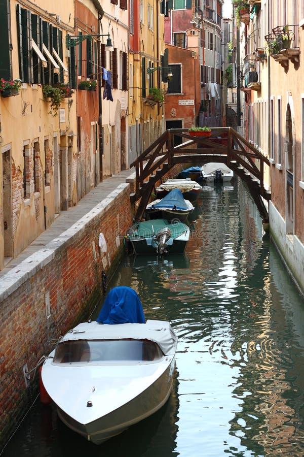 Canal estrecho con el puente y los barcos en Venecia imagen de archivo