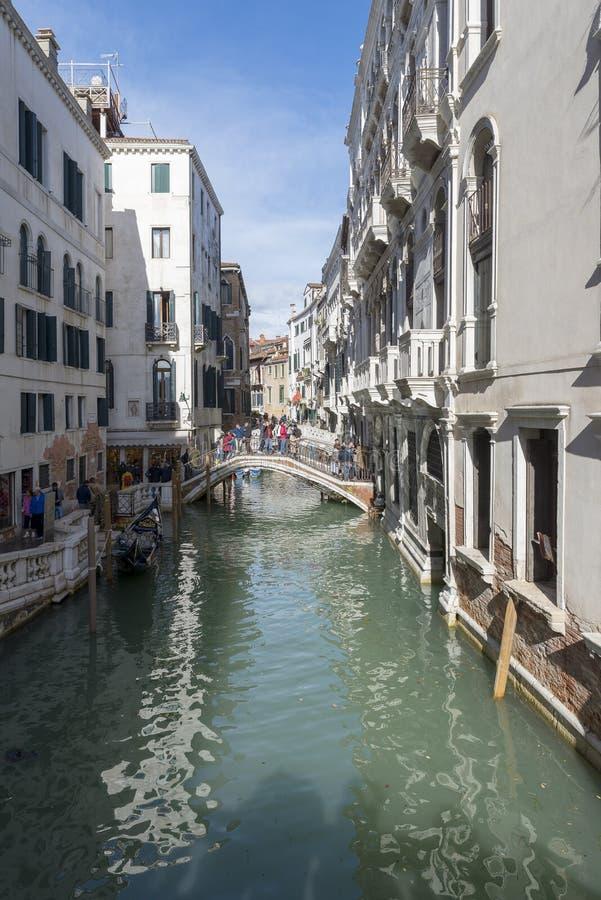 Canal estrecho tradicional con las góndolas en Venecia, Italia imagenes de archivo