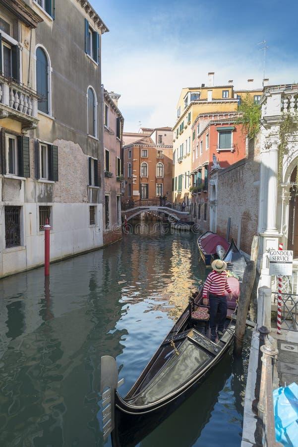 Canal estrecho tradicional con las góndolas en Venecia, Italia fotos de archivo