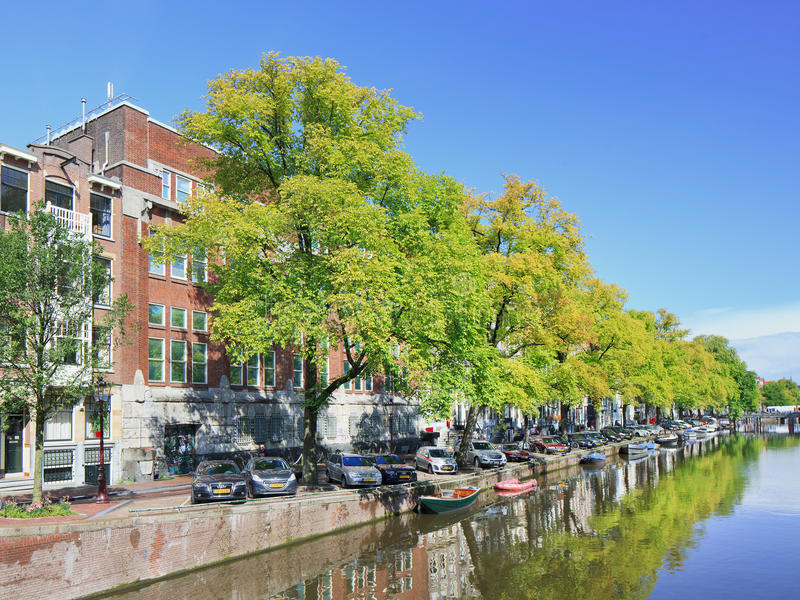 Canal with green trees and a blue sky in Amsterdam, Netherlands. AMSTERDAM-AUGUST 24, 2014. Canal with green trees and a blue sky in Amsterdam canal belt. The stock images
