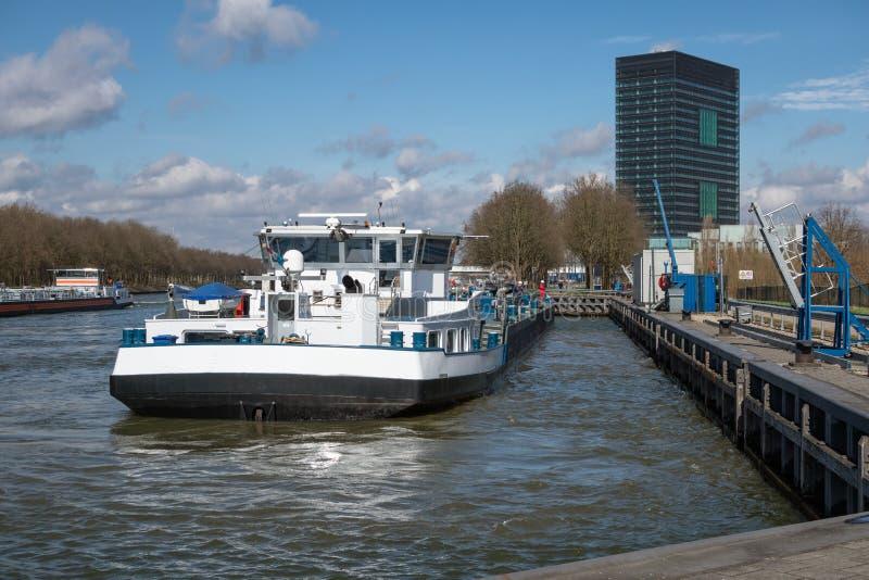 Canal holandés de Amsterdam-Rijn con el amarre de la nave en el punto del tránsito del aceite foto de archivo