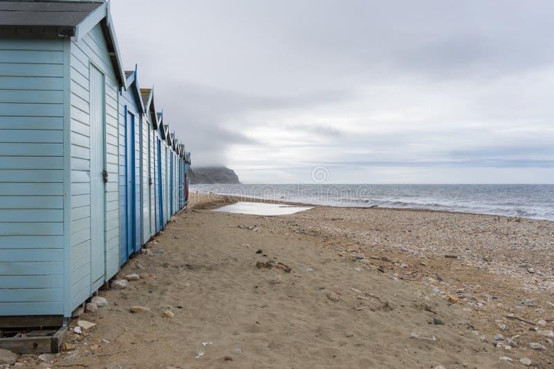 Canal inglês da casa de férias azul da praia na costa jurássico Charmouth, Dorset, Reino Unido imagem de stock