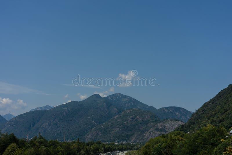 Canal lateral ao maggiore do lago no ascona com pedras da água e nas árvores com fundo da montanha imagens de stock royalty free