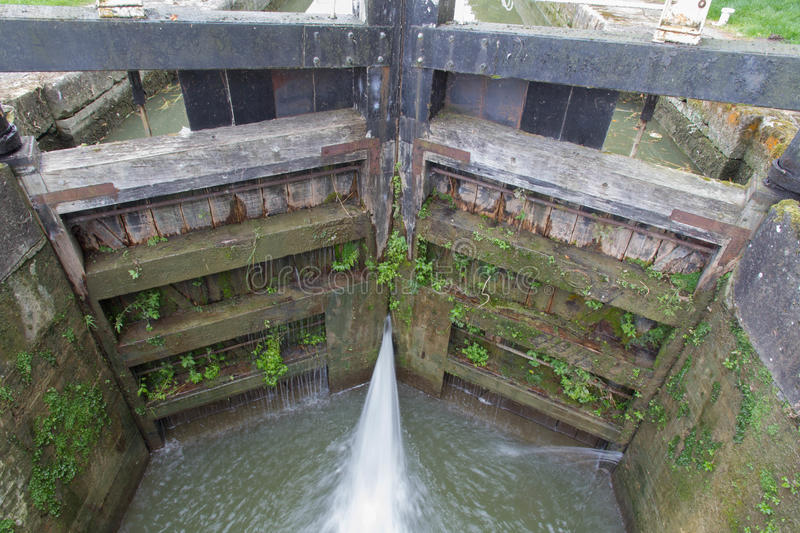 Canal lock, bottom gates with water leaking. Water spraying through gates of canal lock. Bottom gates of full lock. Kennett and Avon Canal, Devizes, Wiltshire royalty free stock image