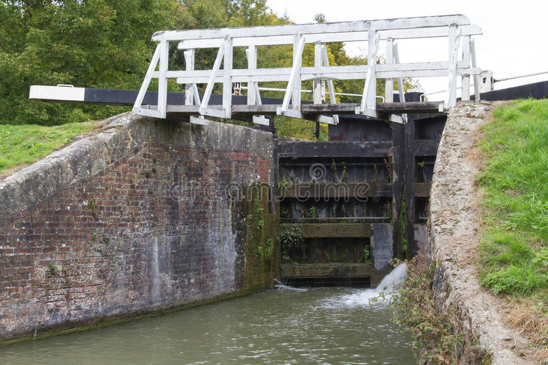 Canal lock with footbridge, Kennett and Avon Canal. Water spraying through gates of canal lock. Bottom gates of full lock. Kennett and Avon Canal, Devizes royalty free stock photo