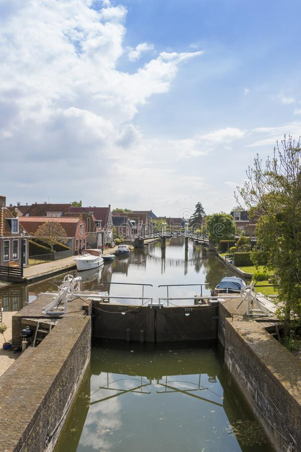 A canal with lock in a historical city in the lake side district of the Netherlands. Hindeloopen, one of the eleven cities in the province of Friesland in the royalty free stock images