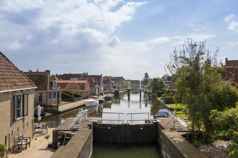 A canal with lock in a historical city in the lake side district of the Netherlands. Hindeloopen, one of the eleven cities in the province of Friesland in the royalty free stock photo