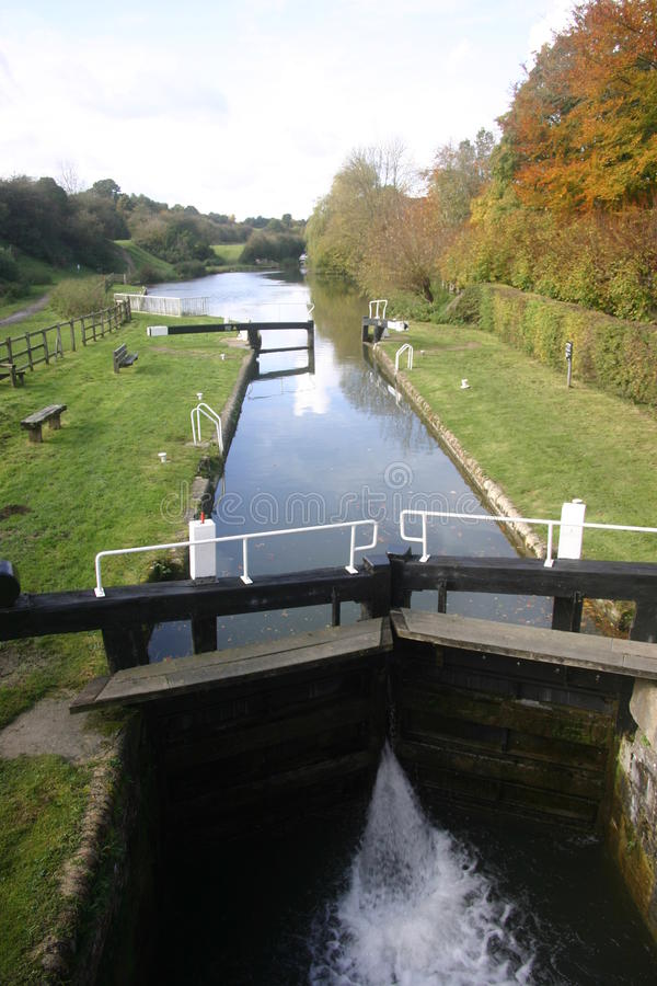 Canal with lock. And gates open at the far end. Surrounded by grass banks. Pale blue sky in the distance. Viewed from a bridge overlooking the lock stock photography