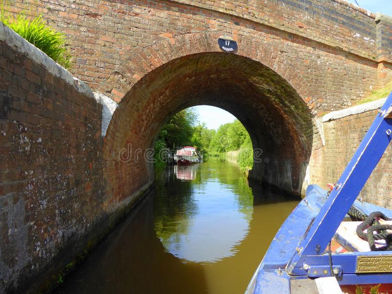 Canal narrowboat arriving at bridge. A canal narrowboat about to go under a bridge on the Taunton to Bridgwater Canal in Somerset, England royalty free stock image