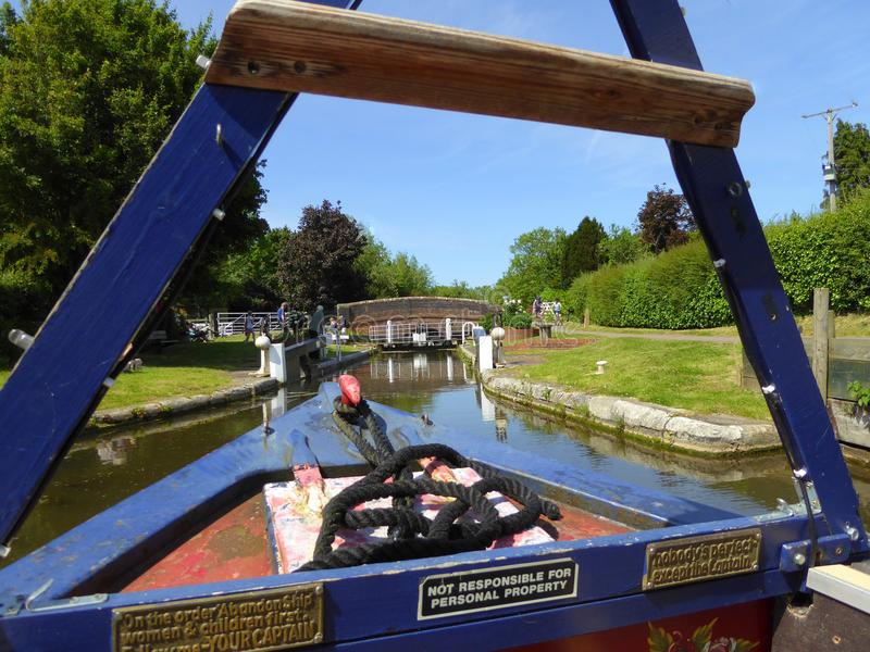Canal narrowboat entering lock gates. A canal narrowboat on the Taunton to Bridgwater Canal about to enter Maunsel Lock in Somerset, England stock image