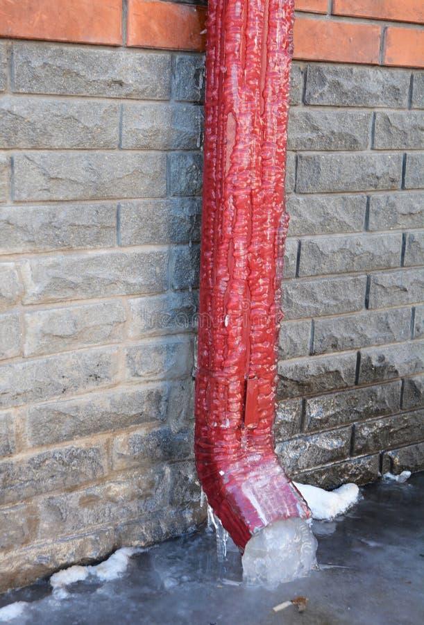 Canal o bajada de aguas congelado Los canales y las bajadas de aguas congelan a veces en bloques sólidos de hielo imagen de archivo libre de regalías