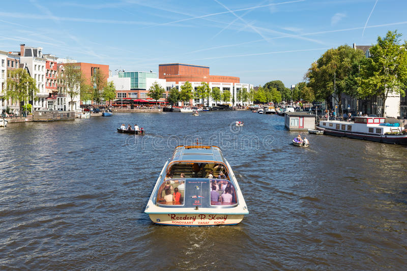 Canal with recreating people in a cruise ship in Amsterdam. AMSTERDAM, THE NETHERLANDS - AUG 06: Canal with recreating people in a cruise ship on August 06, 2015 royalty free stock photos